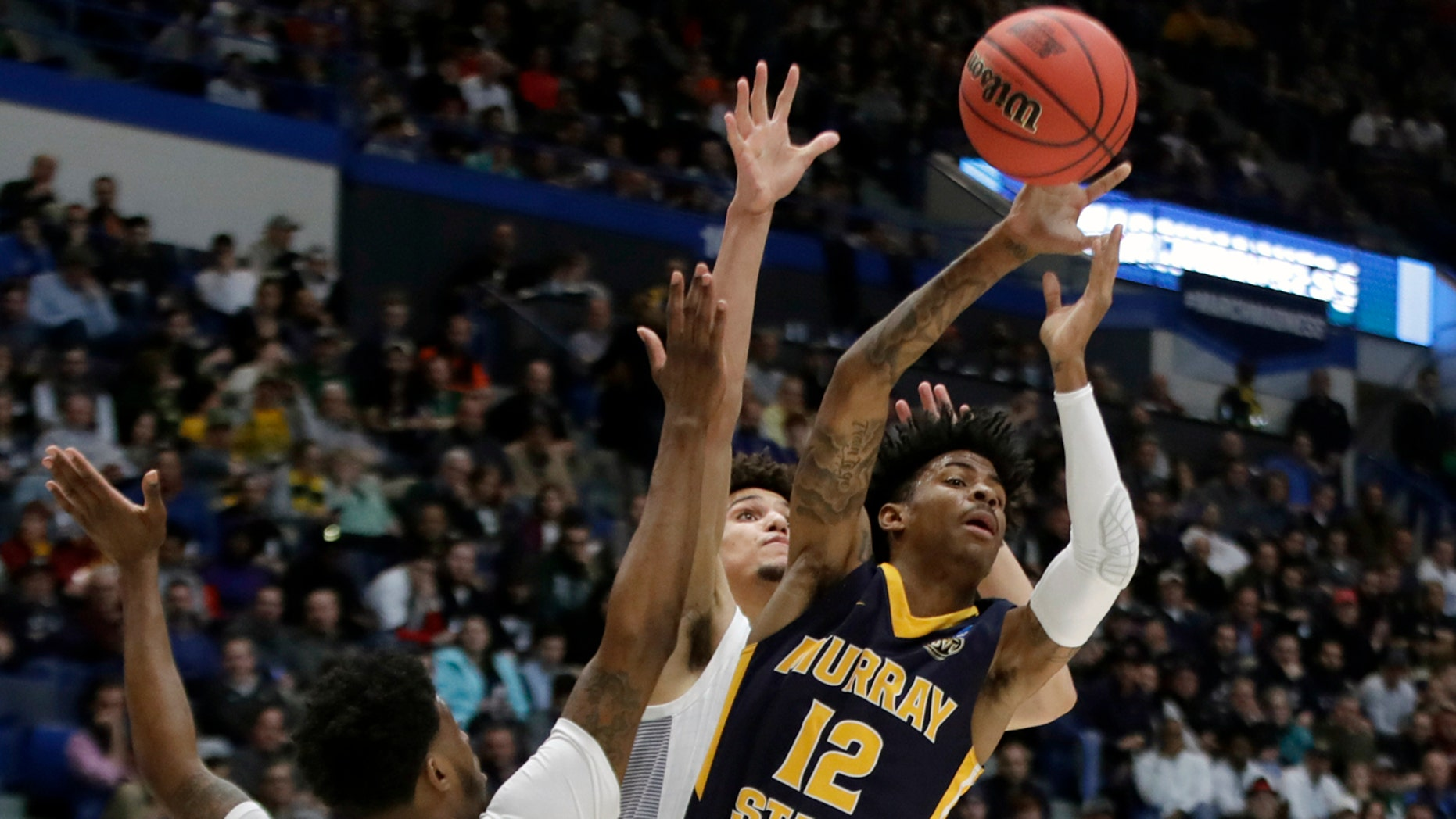 Murray State's Ja Morant (12) passes the ball under pressure from Marquette's Sacar Anim and Brendan Bailey, behind, during the first half of Thursday's game. (AP Photo/Elise Amendola)