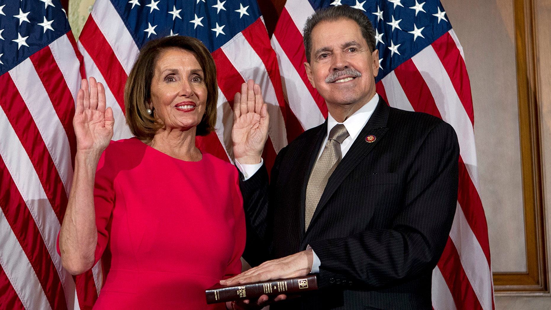 FILE - In this Jan. 3, 2019, file photo, House Speaker Nancy Pelosi of Calif., administers the House oath of office to Rep. Jose Serrano, D-N.Y., during a ceremonial swearing-in on Capitol Hill in Washington, during the opening session of the 116th Congress. Serrano, a 16-term Democrat from the South Bronx, says he has Parkinson's Disease and will retire at the end of his term. (AP Photo/Jose Luis Magana, File)
