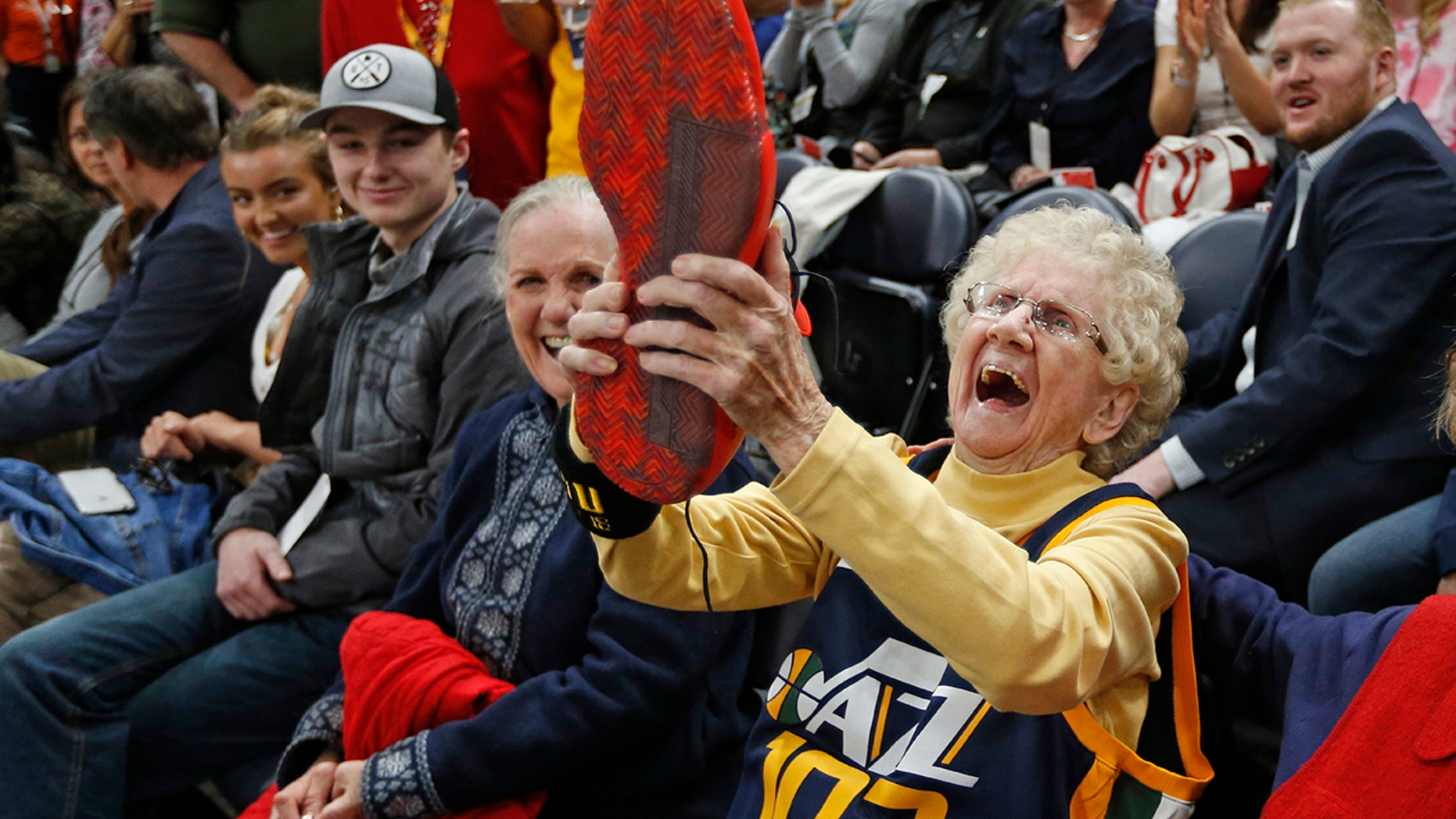 Roberta Morgan, 102, celebrates after Utah Jazz guard Donovan Mitchell handed his basketball shoe to her after he warmed up for the team's NBA basketball game against the Milwaukee Bucks on Saturday, March 2, 2019, in Salt Lake City.