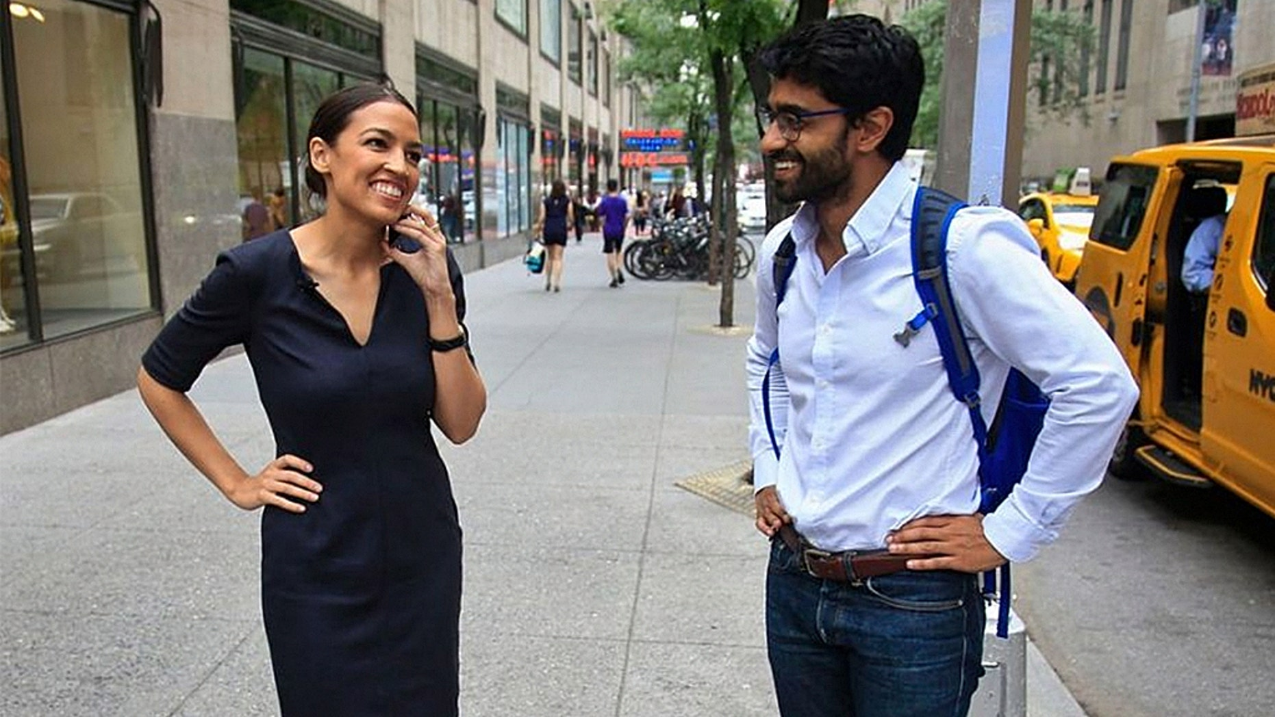 Alexandria Ocasio-Cortez, left, the winner of the Democratic primary in New York's 14th Congressional District, speaks on a phone as Saikat Chakrabarti, her senior campaign adviser stands by, Wednesday, June 27, 2018, in New York.