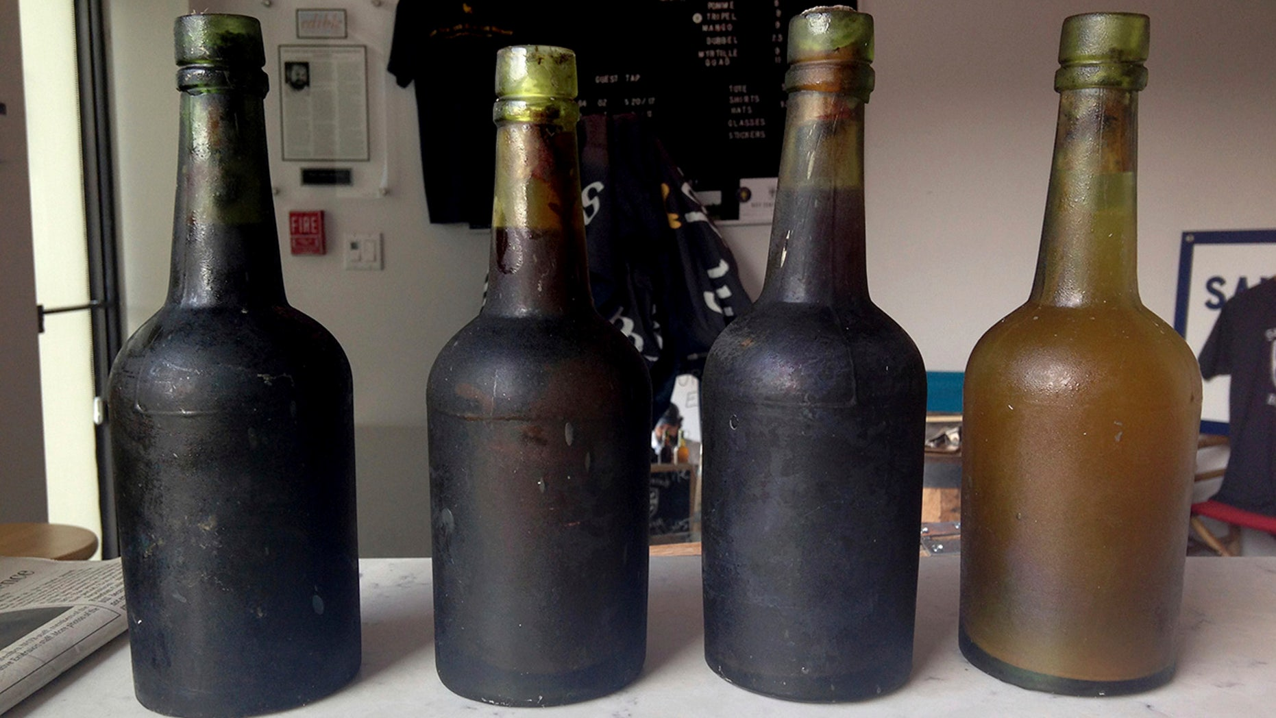 In this July 17, 2017 photo provided by Jamie Adams, four bottles recovered from the SS Oregon, a 133-year-old shipwreck, are shown at the Saint James Brewery in Holbrook, N.Y.