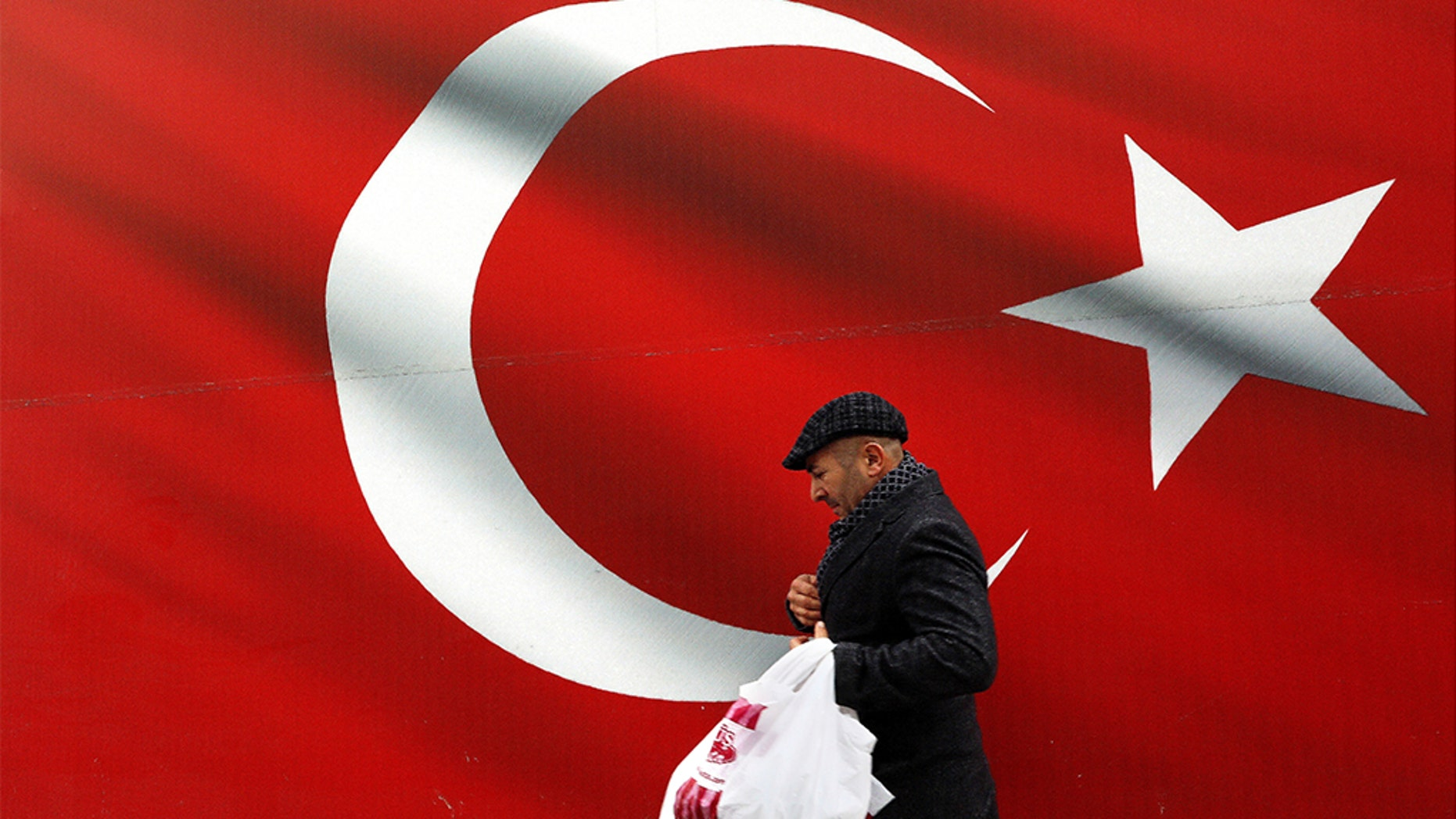 A man walking by a giant Turkish flag in Ankara, Turkey, on Sunday. Turkish citizens have begun casting votes in municipal elections for mayors, local assembly representatives and neighborhood or village administrators. (AP Photo/Ali Unal)