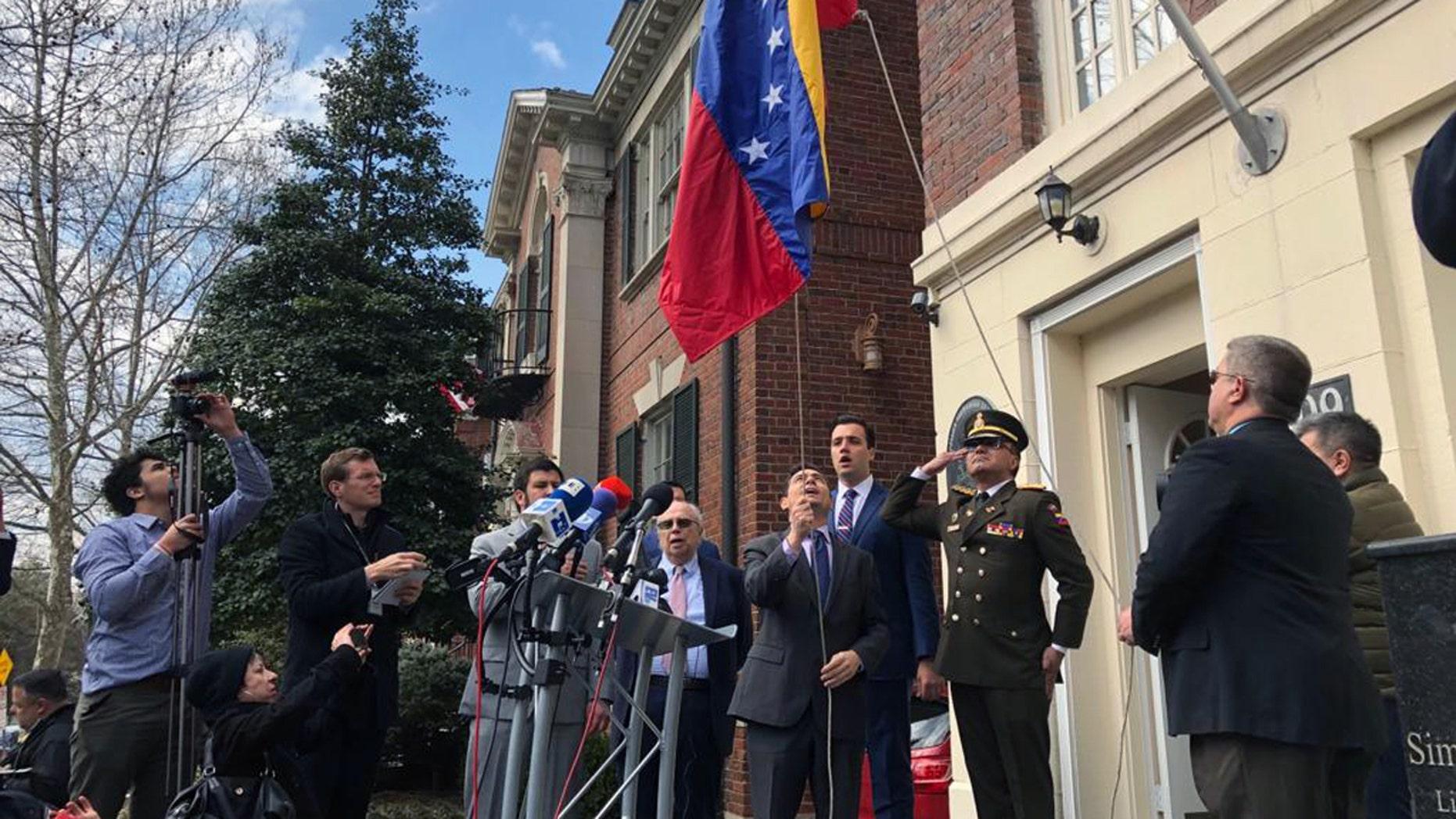 Juan Guaido's United States Ambassador Carlos Vecchio hoists a Venezuelan flag in front of a building of the Venezuelan Ministry of Defense in Washington, DC.