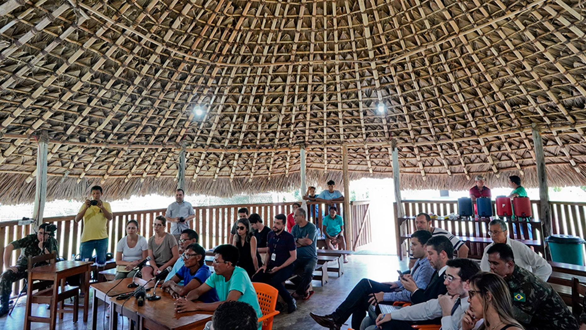 "Temehe Tomas Waimiri, sitting center left and wearing blue shirt and glasses, gives testimony about alleged crimes committed by the Brazilian dictatorship in the 1970s, during a hearing inside a traditional ""maloca"" indigenous hut, at the Waimiri-Atroari reserve in Amazon state, Wednesday, Feb. 27, 2019.  (AP Photo/Victor R. Caivano)"