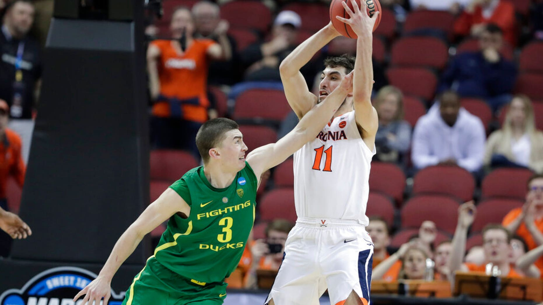 Virginia's Ty Jerome (11) is fouled by Oregon's Payton Pritchard (3) during the second half of a men's NCAA Tournament college basketball South Regional semifinal game. (Associated Press)