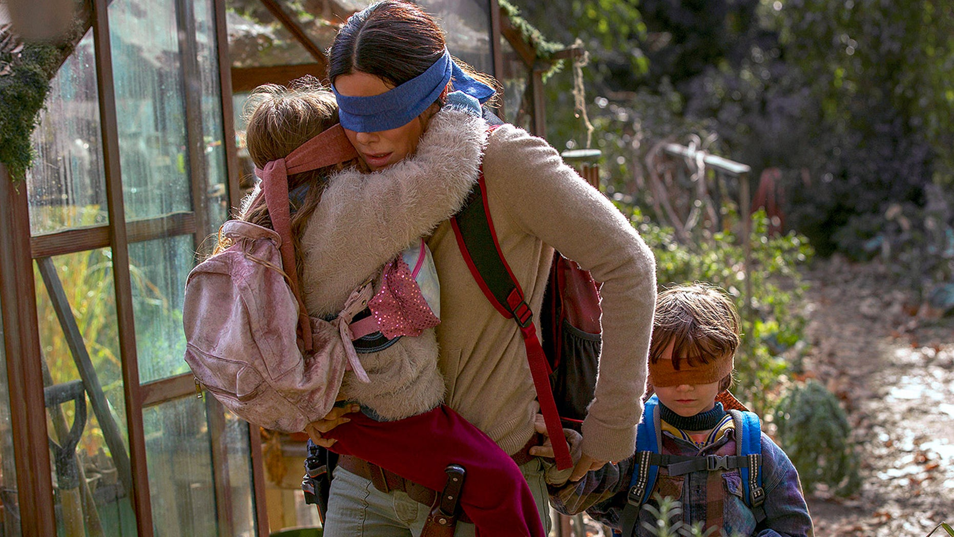 "This image released by Netflix shows Sandra Bullock in a scene from the film, ""Bird Box."" Netflix will remove footage of a real fiery train disaster from its hit post-apocalyptic survival film ""Bird Box"" months after the streaming giant was criticized for exploiting a tragedy. The stock footage was taken from a 2013 crash in the Quebec town of Lac-Megantic when a train carrying crude oil came off the tracks and exploded into a massive ball of fire, killing 47 people. (Saeed Adyani/Netflix via AP)"