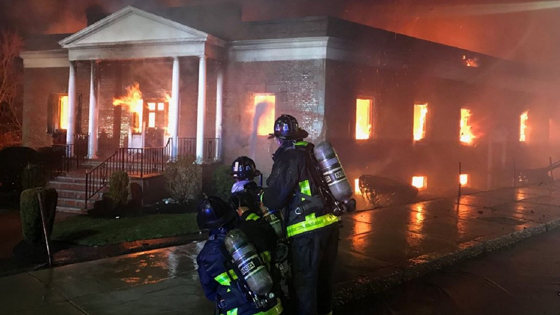Firefighters battle a 9-alarm fire at New England Casket Company on Friday.
