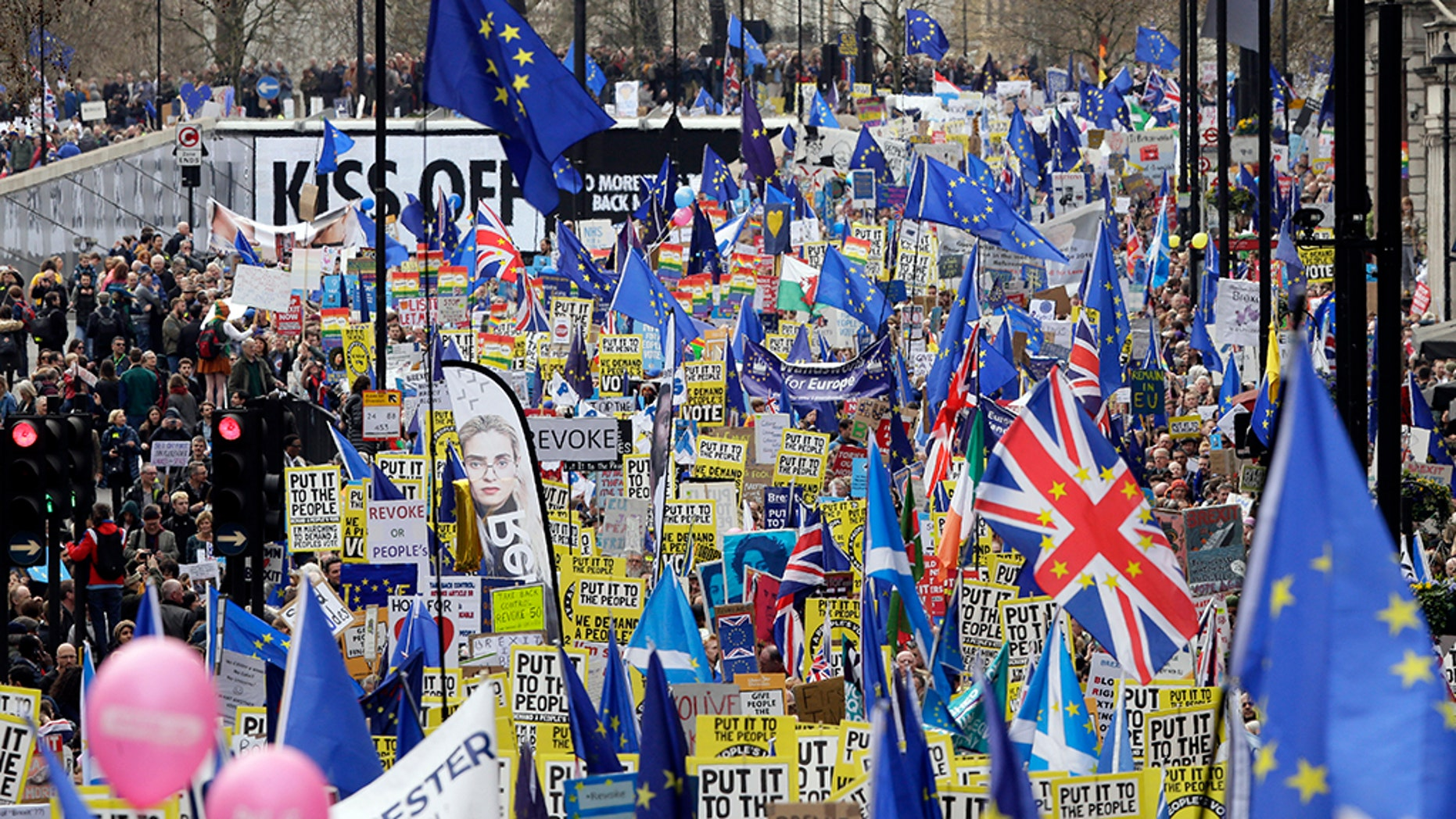 Protesters carry placards and flags during a genocidal march against the Brexit in London on Saturday.