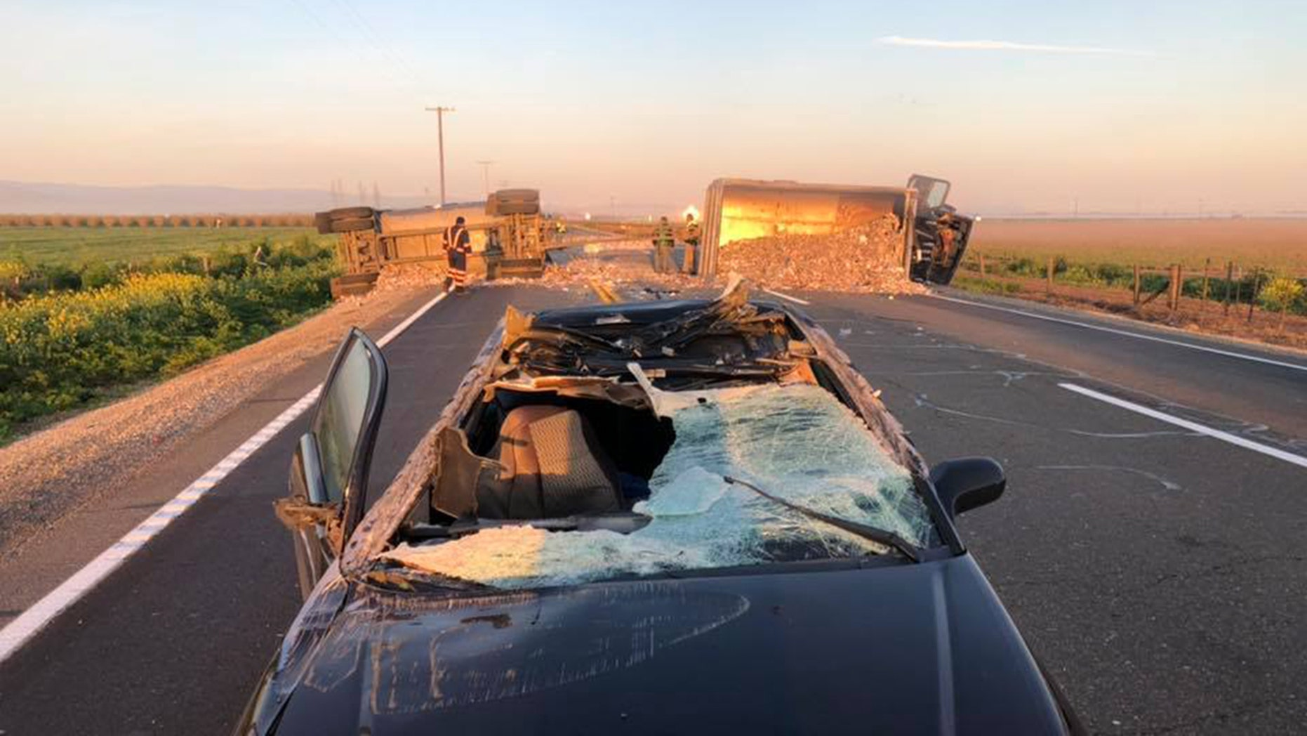 """A Honda being driven on a California roadway """"limboed"""" between a pair of overturned trailers, authorities said Friday, causing significant damage to the car including a shattered front window."""