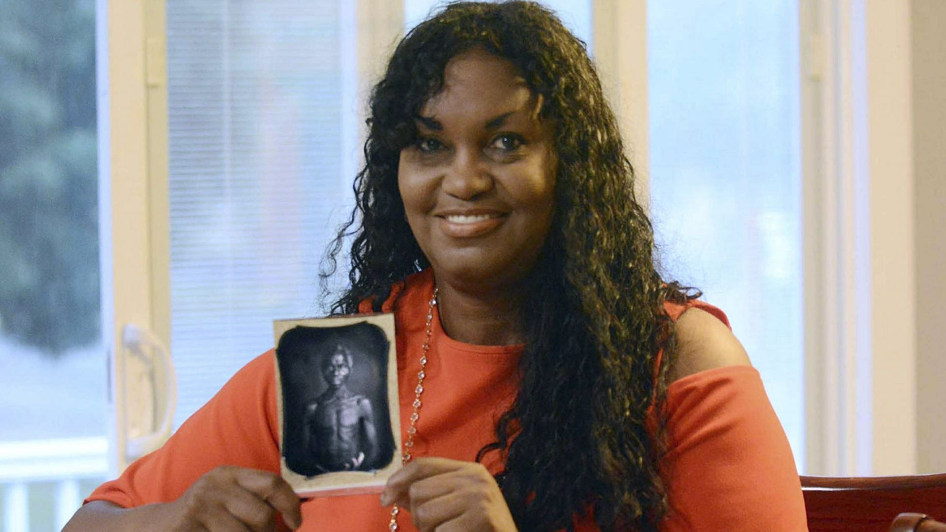 In this July 17, 2018, photo, Tamara Lanier holds an 1850 photograph of Renty, a South Carolina slave who Lanier said is her family's patriarch, at her home in Norwich, Conn. The portrait was commissioned by Harvard biologist Louis Agassiz, whose ideas were used to support the enslavement of Africans in the United States. Lanier filed a lawsuit on Wednesday, March 20, 2019 in Massachusetts state court, demanding that Harvard turn over the photo and pay damages.