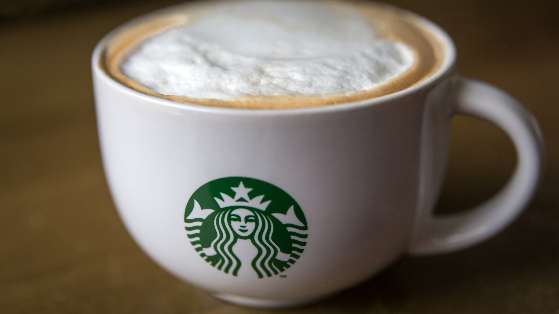Close up of a Starbucks branded Cappucino Mug on a brown table.