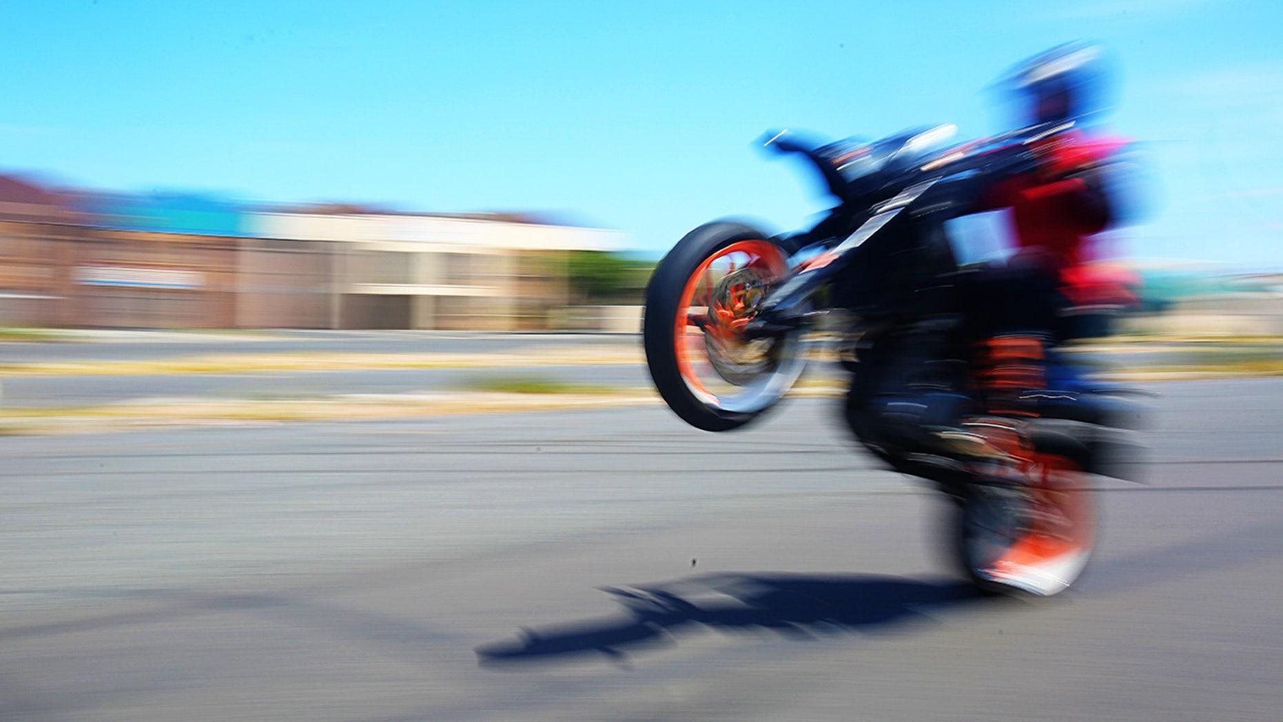 Biker pops a wheelie on asphalt street with blurred motion