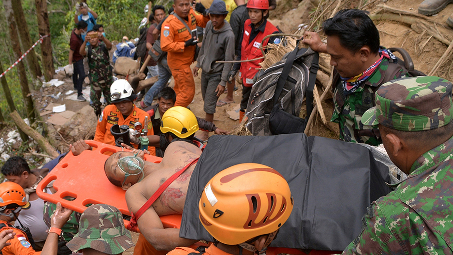 Rescuers carry a survivor of a collapsed mine on a stretcher in Bolaang Mongondow, North Sulawesi, Indonesia, on Thursday.