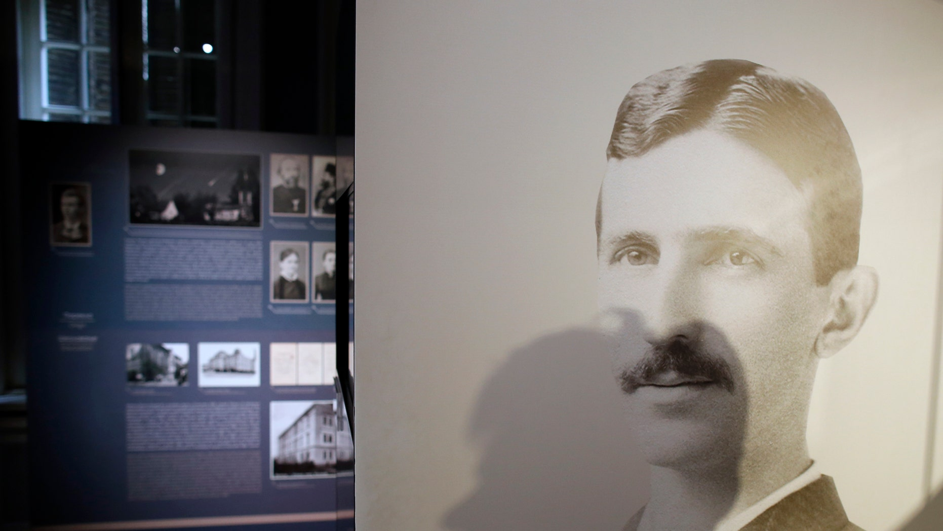 A shadow of Milica Kesler, curator and archivist is cast onto a poster of Nikola Tesla at the Nikola Tesla museum in Belgrade, Serbia, Thursday, March 7, 2019. A private culture society in Serbia has made public two letters written by Serb-American inventor and electricity pioneer Nikola Tesla. The Adligat group has told The Associated Press they recently obtained the letters from a collector and verified their authenticity with multiple sources. (AP Photo/Darko Vojinovic)