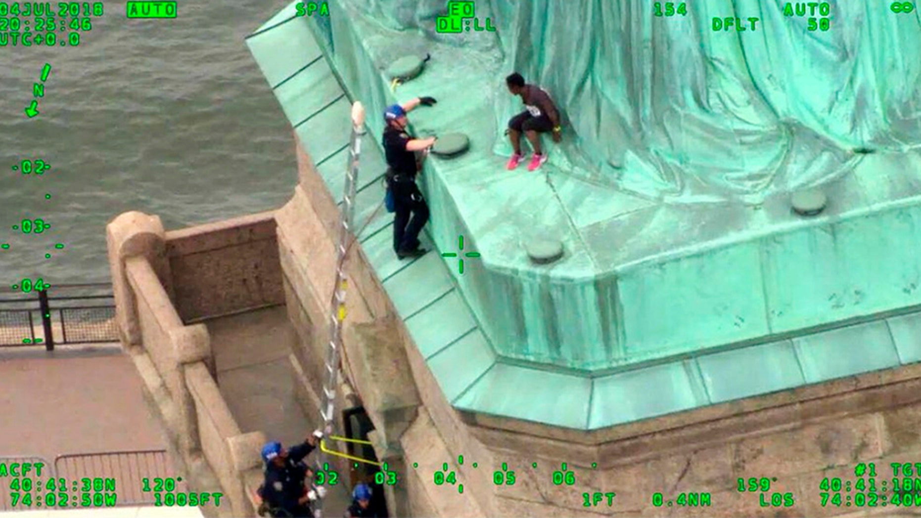 In this July 2018, frame from video provided by the New York City Police Department, members of the NYPD Emergency Service Unit work to safely remove Therese Okoumou, a protester who climbed onto the Statue of Liberty and was charged with misdemeanor trespassing and disorderly conduct. (AP/NYPD)
