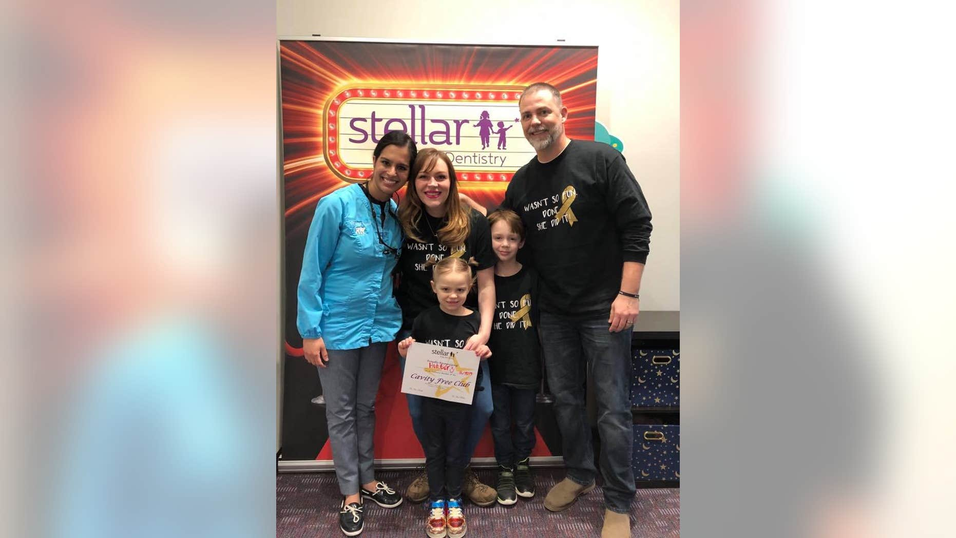Hunter Jones, pictured holding her certificate, is now cancer-free after Dr. Harlyn Susarla, left, ordered a panoramic X-ray which revealed a growing tumor, and set-off 18 months of intense treatment to beat an aggressive cancer.