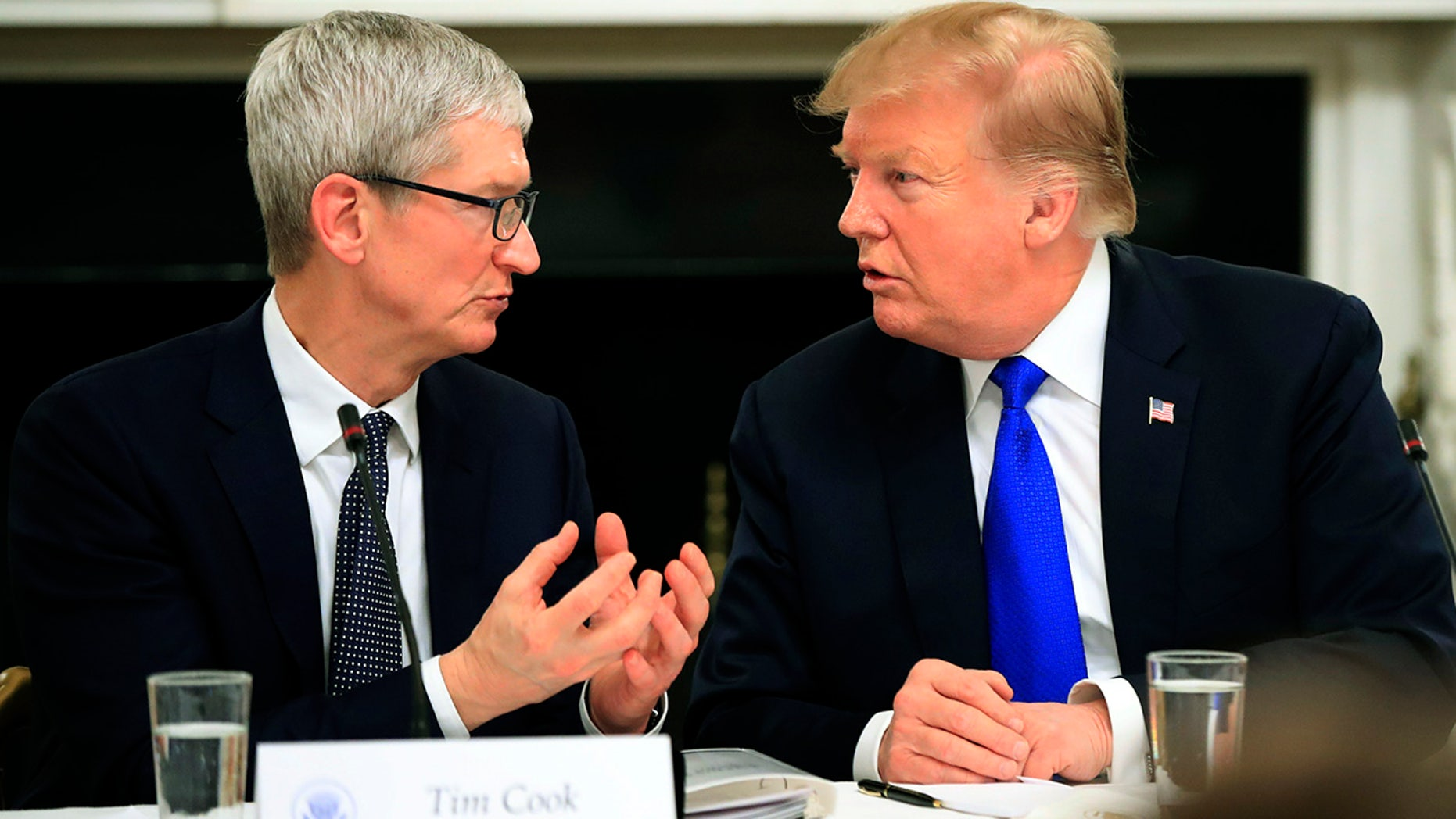 President Donald Trump talks to Apple Inc. CEO Tim Cook during the American Workforce Policy Advisory Board's first meeting in the State Dining Room of the White House in Washington, Wednesday, March 6, 2019. (AP Photo/Manuel Balce Ceneta)