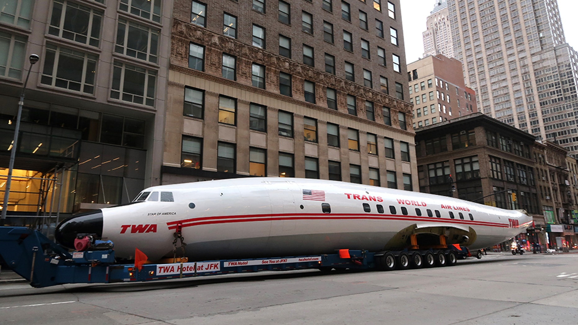 NEW YORK, NY - MARCH 23: The fuselage of a Trans World Airlines airplane is transported up 6th Avenue on March 23, 2019, in New York City. The jet was taken to Times Square and will end up at the new TWA Hotel at JFK airport.