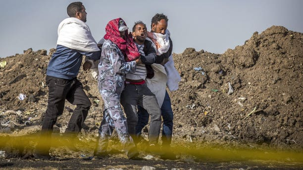 A grieving relative who lost his wife in the crash is helped by a member of security forces and others at the scene where the Ethiopian Airlines Boeing 737 Max 8 crashed shortly after takeoff on Sunday.