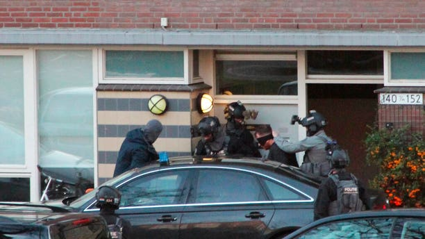 Gokmen Tanis, 37, is led away by police in Utrecht, Netherlands on Monday March 18, after a shooting incident on a tram.