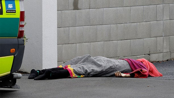 A body lies on the footpath outside a mosque in central Christchurch, New Zealand, on Friday. (AP)