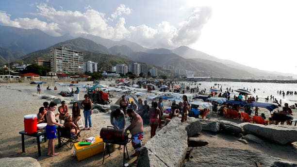 A family from Caracas prepares food during a day trip to Camuri Chico beach in Venezuela on March 1, 2019. The country is gripped by a political crisis that pits leader Nicolas Maduro against Juan Guaido, the opposition chief.