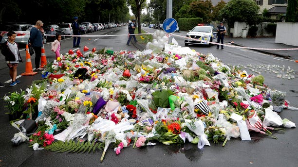 Mourners place flowers as they pay their respects at a makeshift memorial near the Masjid Al Noor mosque in Christchurch, New Zealand, Sunday, March 17, 2019, where one of the two mass shootings occurred.