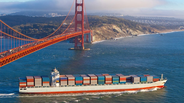 Full container cargo ship sailing out of San Francisco bay under the Golden gate bridge and heading out into the Pacific Ocean in the late afternoon