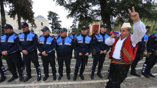A protester dressed in traditional clothing flashes the victory sign in front of Albanian policemen guarding the parliament building in Tirana, on Thursday, March 28, 2019. Albanian opposition protesters have repeated attempts to enter the parliament by force in their protest asking for the government's resignation and an early election. (AP Photo/ Hektor Pustina)