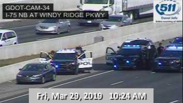 "In this image made from video provided by the Georgia Department of Transportation, Marietta Police block southbound lanes on Interstate-75, near Marietta, Ga., North of Atlanta, Friday, March 29, 2019. Marietta police said in a brief statement that the southbound lanes of Interstate 75 were shut down Friday morning due to a motorist stopped on the freeway just northwest of Atlanta. Police described the motorist as a ""non-compliant driver."" (Georgia Department of Transportation via AP)"