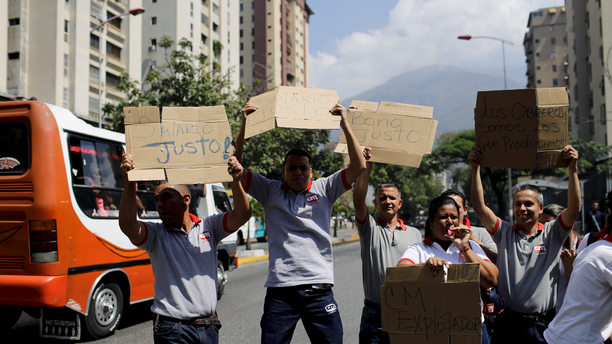 Supermarket employees holds up a pieces of cardboard with a handwritten messages demanding better salaries, in Caracas, Venezuela, Wednesday, March 20, 2019. (AP Photo/Natacha Pisarenko)