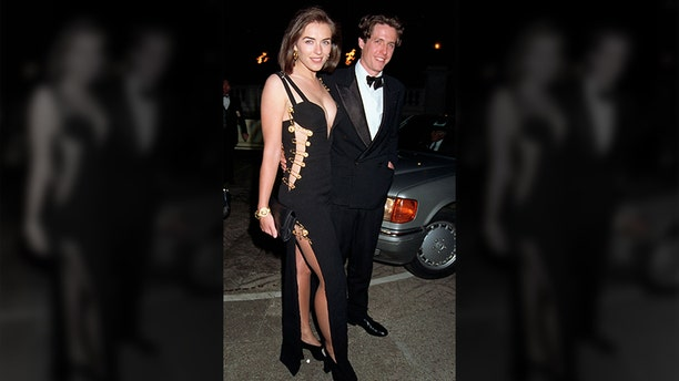 Elizabeth Hurley, pictured with Hugh Grant, wears a Versace dress to the premiere of 'Four Weddings and A Funeral' held in Leicester Square on March 09, 1994 in London, England.