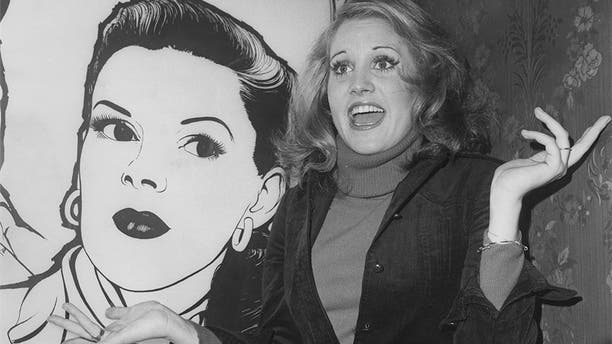 American actress and singer Lorna Luft, daughter of Judy Garland, poses by an autographed painting of her mother during a press reception in the bar of the London Palladium for her show in 1976.