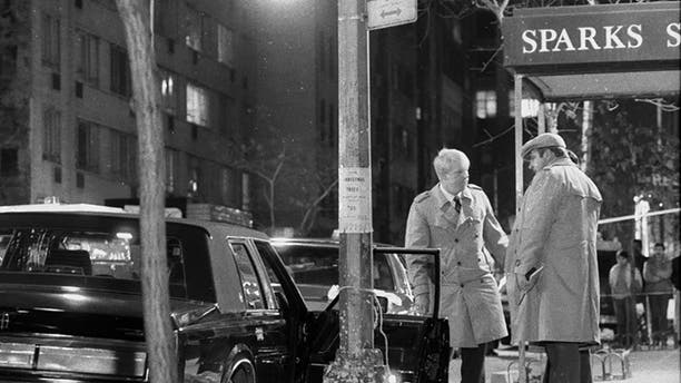 Detectives stand over body of reputed mob boss Paul Castellano, after execution on 46th St. Body of Castellano's chauffeur, Thomas Bilotti, lies partially covered in the street, far left. (Photo By: Tom Monaster/NY Daily News via Getty Images)