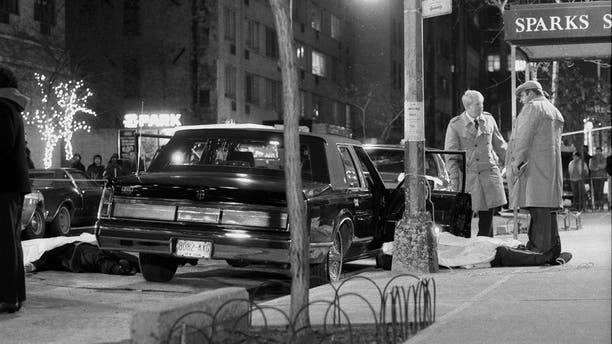 Detectives stand over body of reputed mob boss Paul Castellano, after his execution outside of Spark's Steakhouse on 46th St. in New York City. The body of Castellano's chauffeur, Thomas Bilotti, lies partially covered in the street, far left.