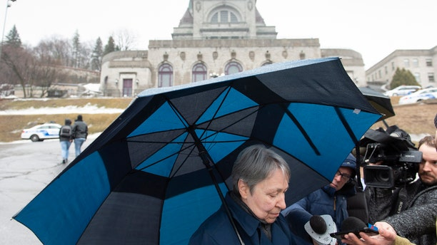 A woman talks to the media at the scene where a Catholic priest was stabbed as he was celebrating morning mass at the St. Joesph's Oratory in Montreal on Friday, March 22, 2019
