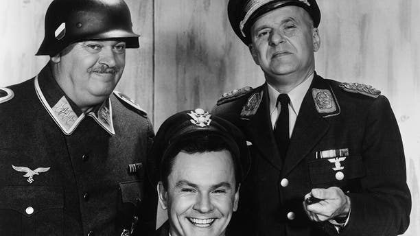 1965: L-R: Austrian actor John Banner, American actor Bob Crane, and German-born actor Werner Klemperer pose together in a promotional portrait for the World War II-set television series, 'Hogan's Heroes'. Banner and Klemperer wear Nazi uniforms, and Crane wears a cap and jacket. (Photo by CBS Photo Archive/Getty Images)