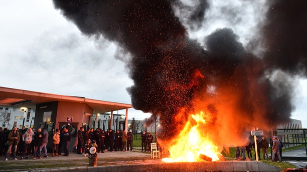 """The entrances to 18 prisons in France were blocked by guards who burned tires and other materials at the gates in protest of thestabbing of two colleagues at a jail in northwest France which is being described as a """"terrorist"""" attack"""