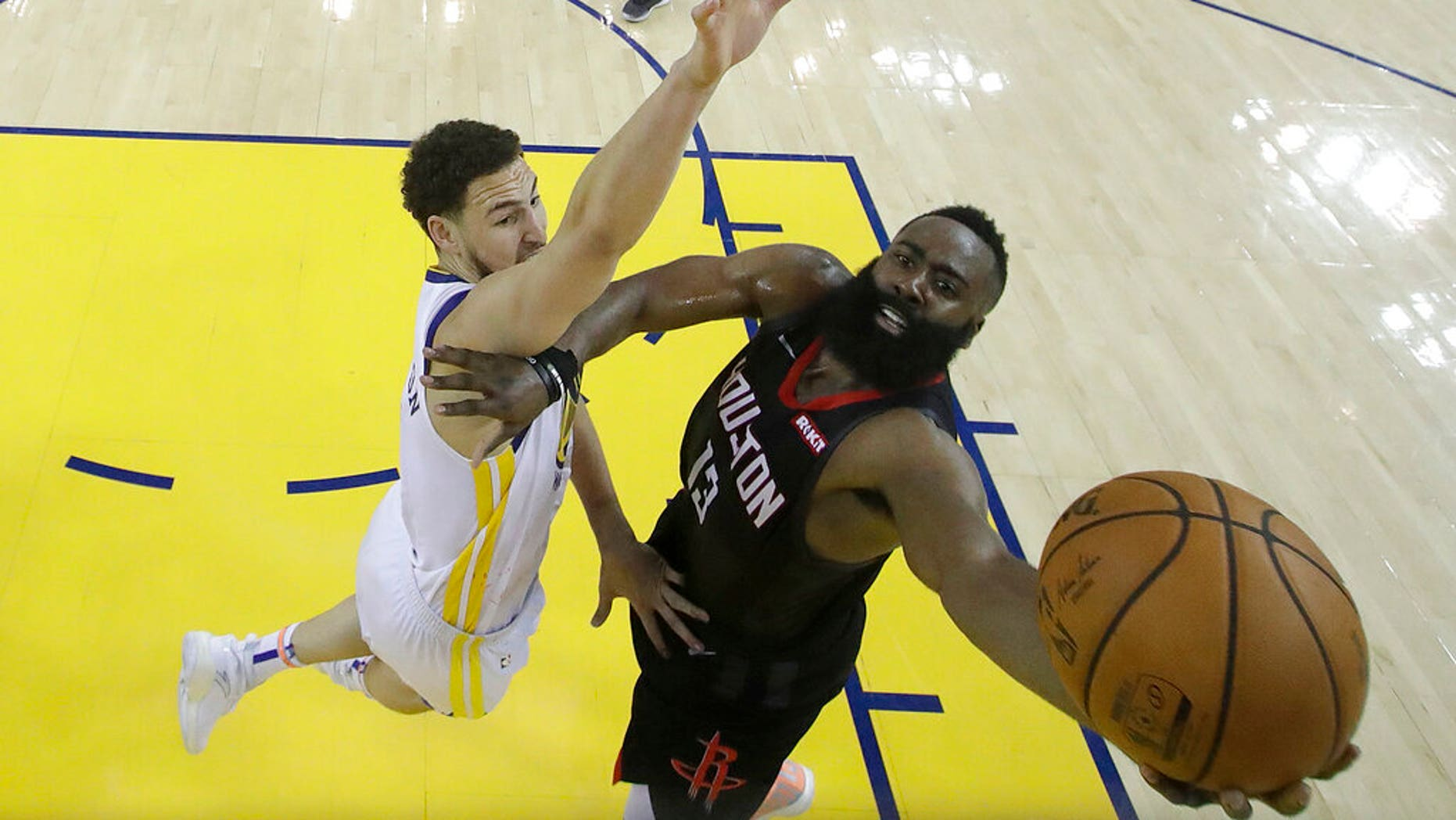 Houston Rockets guard James Harden, right, shoots against Golden State Warriors guard Klay Thompson during the second half of Game 1 of a second-round NBA basketball playoff series in Oakland, Calif.