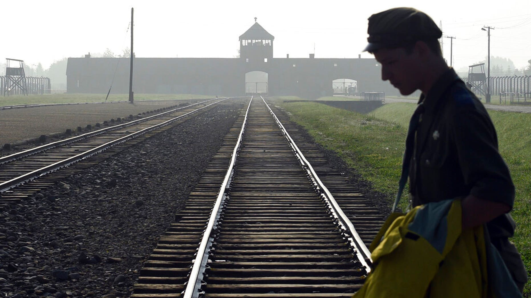 FILE: a man crosses the iconic rails leading to the former Nazi death camp of Auschwitz-Birkenau in Poland.