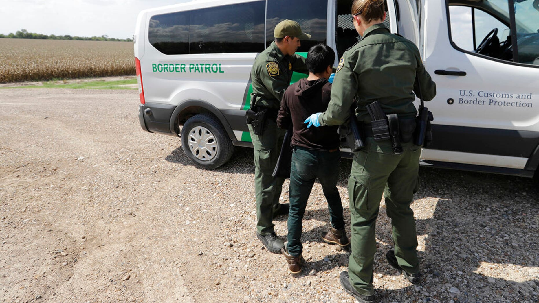 FILE - In this June 25, 2018 file photo, U.S. Border Patrol agents load a migrant from Guatemala into a van after he was caught trying to enter the United States illegally in Hidalgo, Texas. (AP Photo/David J. Phillip)