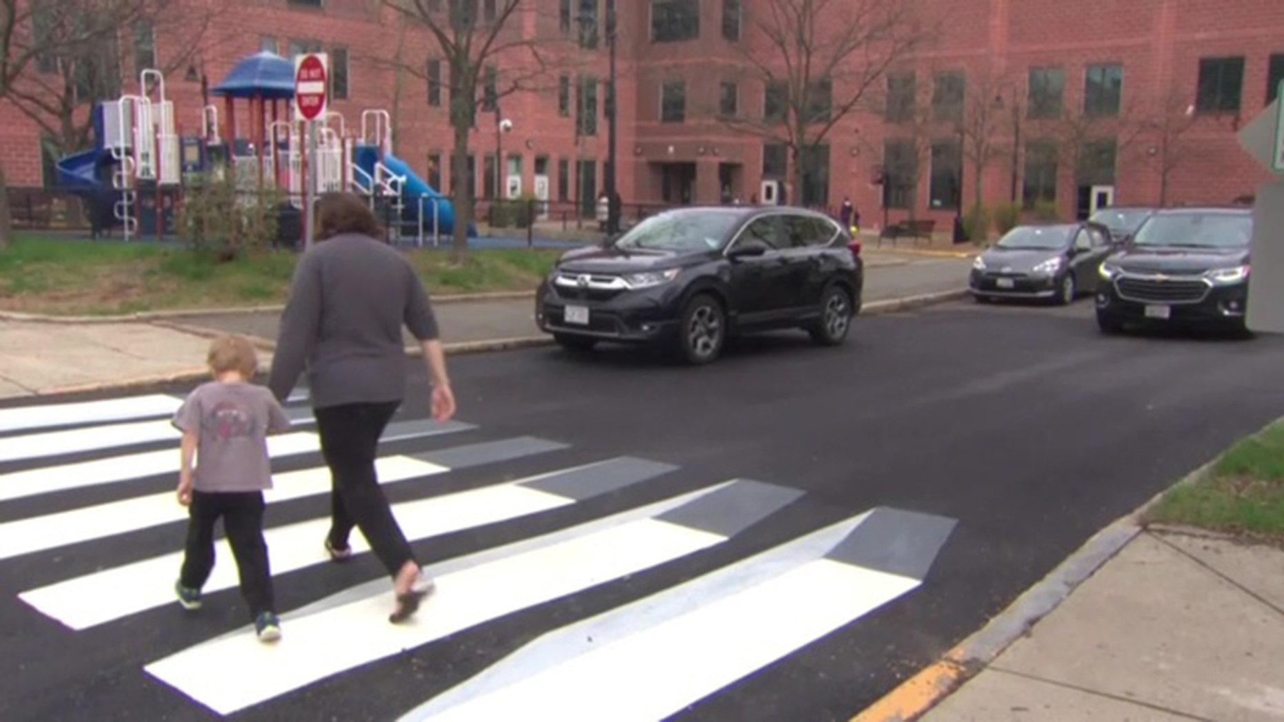 A pedestrian walks across the newly designed 3D crosswalk. The walkway was designed by a pair of fourth graders in Massachusetts.