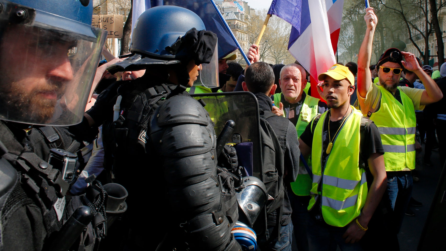 Riot policeman stand by as French yellow vest protesters are rallying to support an older woman activist injured in a confrontation with police, Saturday, March 30, 2019 in Paris. In 2019, 24 police officers in France have committed suicide, raising alarm over increased demand on the nation's police force.