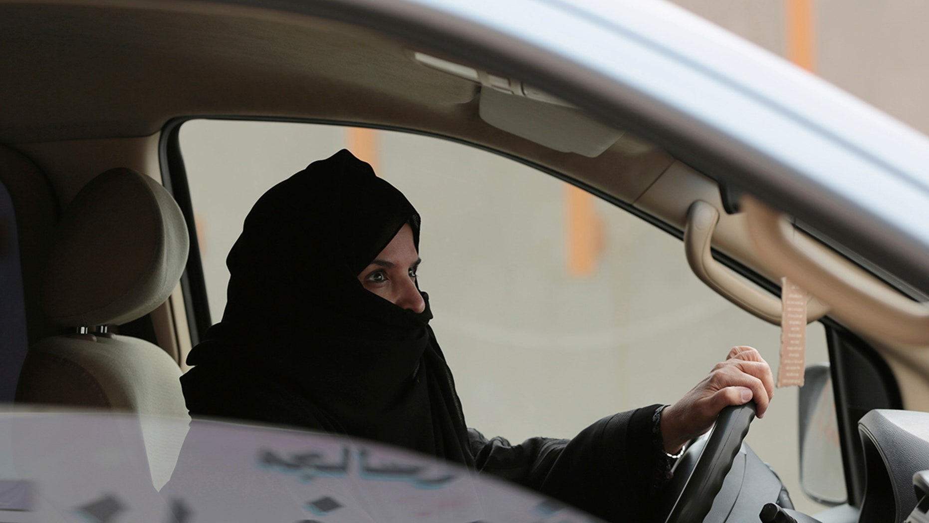 FILE - In this March 29, 2014 file photo, Aziza al-Yousef drives a car on a highway in Riyadh, Saudi Arabia, as part of a campaign to defy Saudi Arabia's then ban on women driving. Nearly a dozen Saudi women's rights activists, most of them imprisoned, have attended their third court session Wednesday, April 3, 2019, and were told their trials will continue for at least two more weeks. Meanwhile, three women who were granted temporary release last week, among them al-Yousef and Eman al-Najfan, were told their next court date would take place after the Muslim holy month of Ramadan, which coincides with early June. (AP Photo/Hasan Jamali, File)