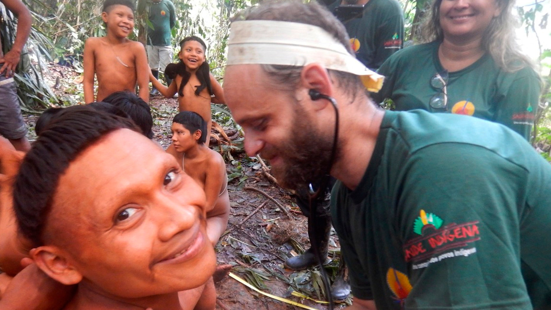 In this 2019 handout photo released by Brazil's National Indian Foundation, or FUNAI, a Korubo man smiled as a FUNAI member checked his heart rate during an expedition to the Javari Valley.