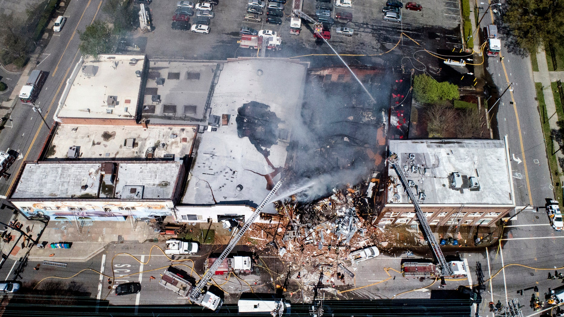 In this aerial photo, firefighters battle a fire at the scene of an explosion in Durham, N.C. Wednesday, April 10, 2019. ()