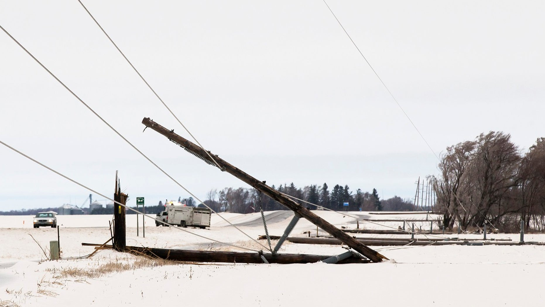 A row of power line poles are snapped from ice and wind along Hwy. 56 south of Interstate 90 on Thursday, April 11, 2019, near Browndale, Minn. A powerful spring snow storm is creating hazardous travel conditions in parts of the Midwest and Great Lakes regions. (Andrew Link/The Rochester Post-Bulletin via AP)