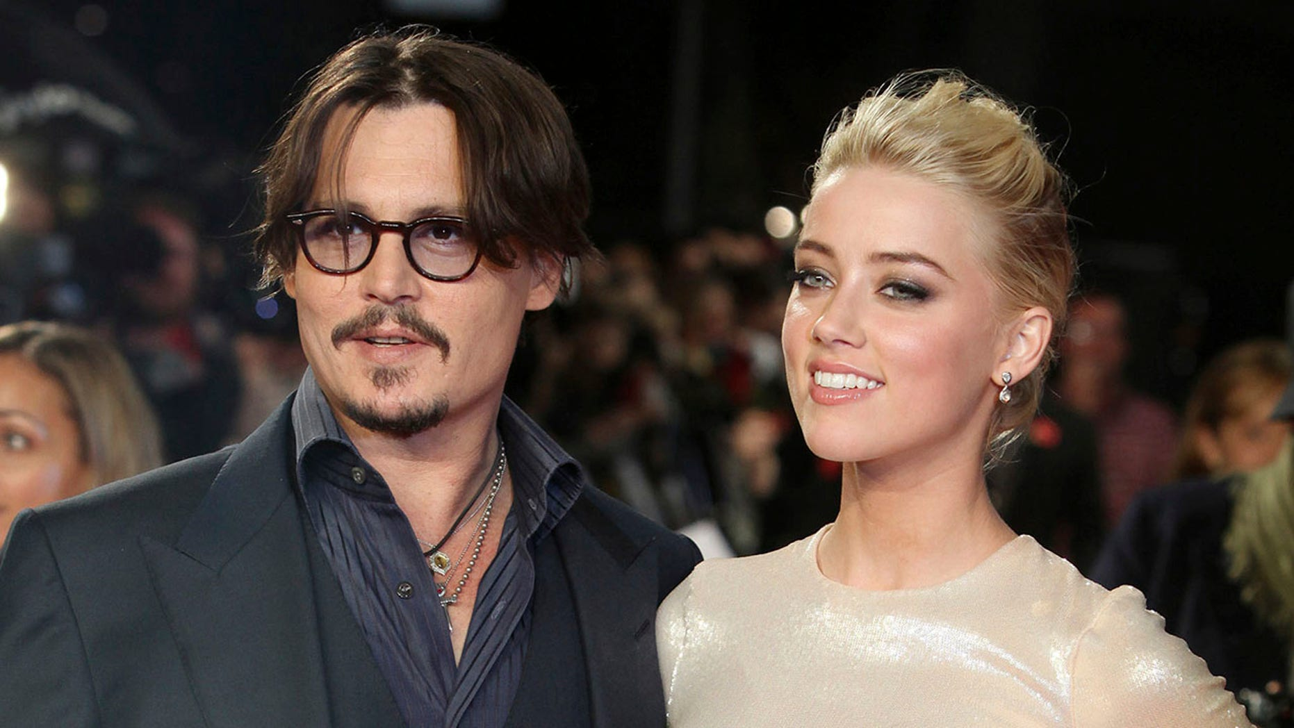 """Johnny Depp, left, and Amber Heard arrive for the European premiere of their film, """"The Rum Diary,"""" in London."""