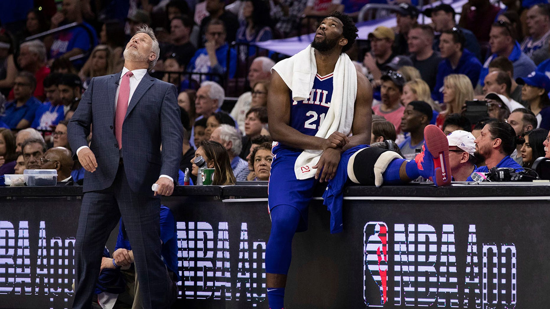 Philadelphia 76ers head coach Brett Brown, left, and Joel Embiid, right, of Cameroon, look up at the scoreboard during the first half in Game 1 of a first-round NBA basketball playoff series against the Brooklyn Nets, Saturday, April 13, 2019, in Philadelphia. The Nets won 111-102. (Associated Press)