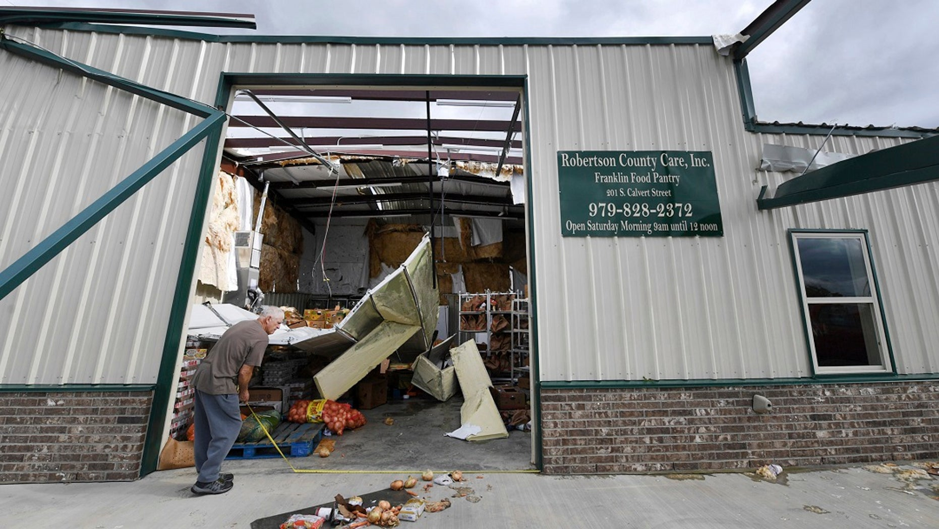 Jerry Redden takes a measurement outside Robertson County Care, Inc., after the food pantry was hit by a powerful storm, Saturday in Franklin, Texas. (Associated Press)